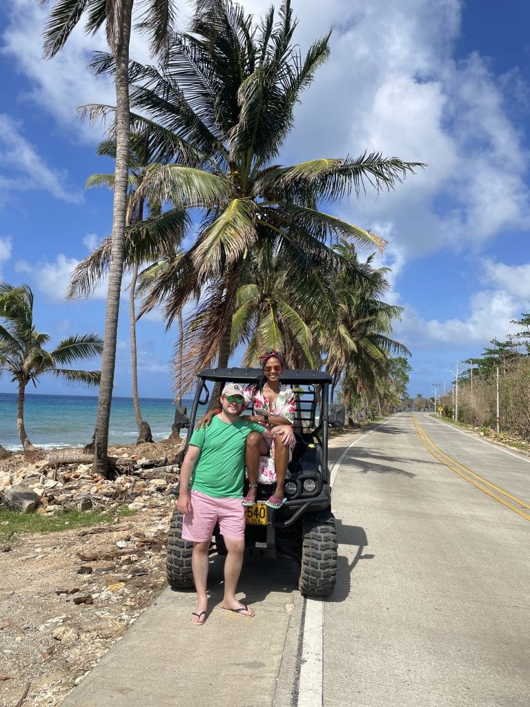 Photo of a couple sitting on the hood of a golf cart, one of the top things to do in San Andres, Colombia.