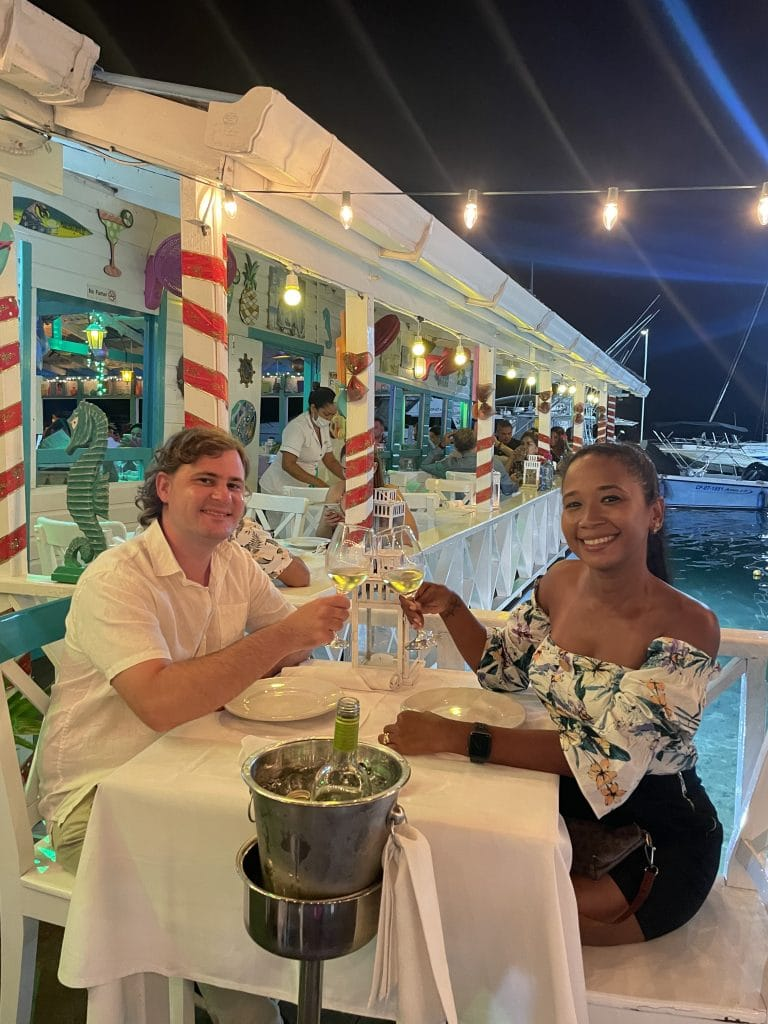 Photo of a couple cheersing wine glasses at a table at La Regatta, one fo the best places to eat in San Andres.