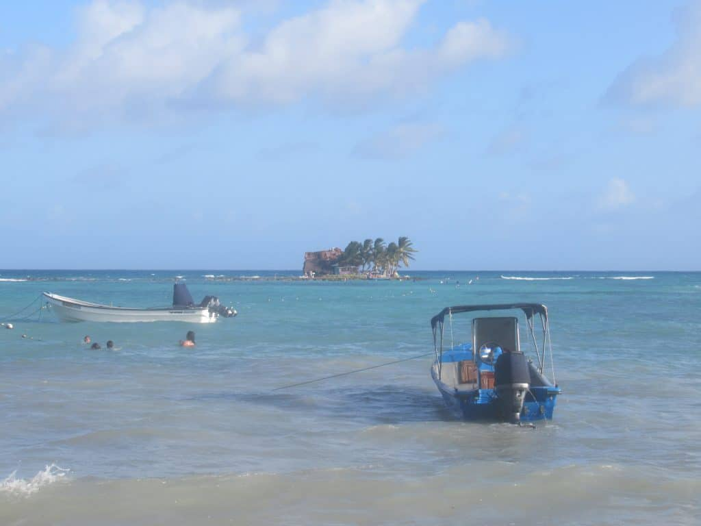 A photo of some boats tied up with Rocky Cay Island, San Andres, behind it.