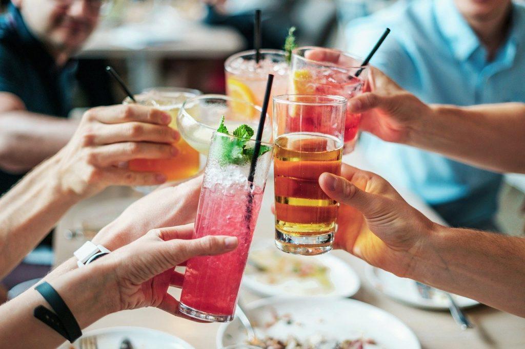 Photo of people cheersing drinks.